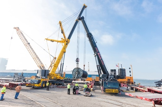 Cranes holding a 230,000 pound reel full of electrical cable