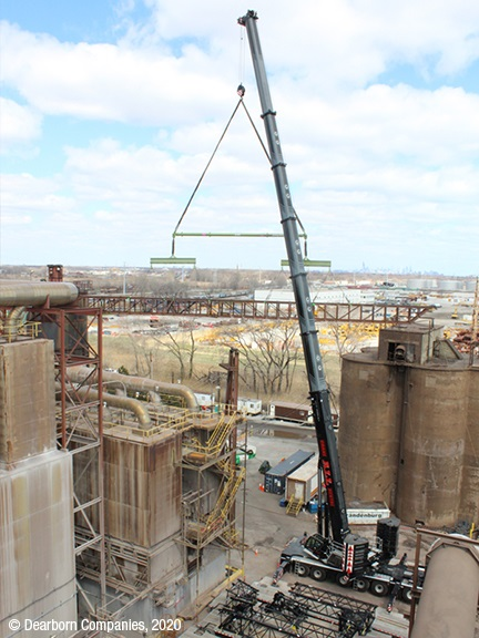 Two cranes pick and hold active plant's conveyor bridge during demolition process