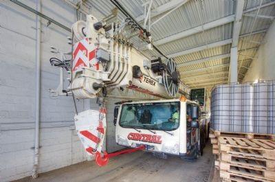 120-ton Terex AC 100/4(L) all-terrain crane driving through a narrow tunnel